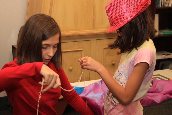 (l.-r.) Miriam Crane & Emma Berg create beautiful tallit during our religious school tallit making program.